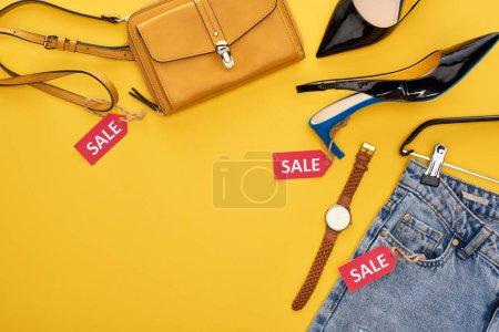 Photo pour Vue aérienne des vêtements et accessoires à la mode avec étiquettes de vente sur fond jaune - image libre de droit