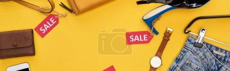 Photo pour Vue d'ensemble des vêtements et accessoires à la mode avec étiquettes de vente sur fond jaune, photo panoramique - image libre de droit