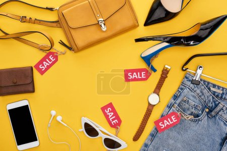 Photo for Top view of fashionable clothing and accessories with sale labels and smartphone with earphones on yellow background - Royalty Free Image