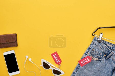 Photo for Top view of fashionable clothing and accessories with smartphone and sale labels on yellow background - Royalty Free Image