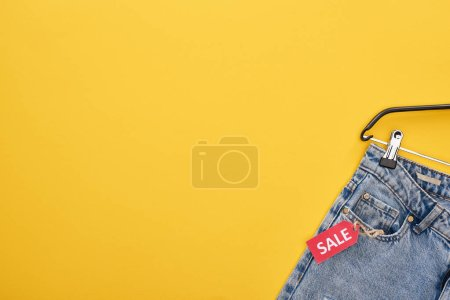 Photo pour Top view of fashionable jeans with sale label on yellow background - image libre de droit