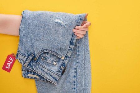 Photo pour Crochet vue d'une femme tenant des jeans avec une étiquette de vente sur fond jaune - image libre de droit