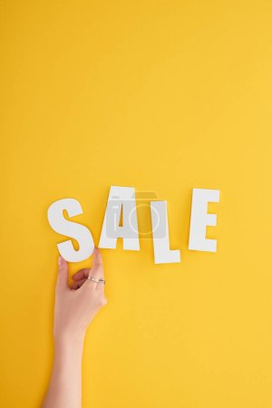 Photo pour Cropped view of woman holding sale lettering on yellow background - image libre de droit