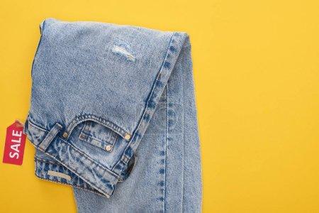 Photo pour En haut des jeans avec étiquette de vente sur fond jaune - image libre de droit