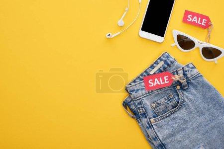 Photo pour En haut des jeans, lunettes et smartphone avec écouteurs avec étiquettes de vente sur fond jaune - image libre de droit
