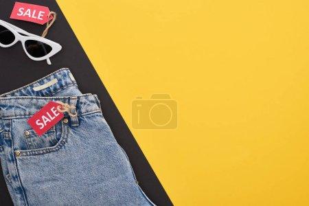 Photo pour En haut des jeans et des lunettes avec des étiquettes de vente sur fond jaune et noir - image libre de droit