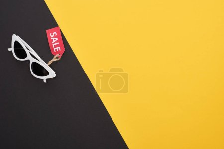 Photo pour Top view of glasses with sale label on yellow and black background - image libre de droit