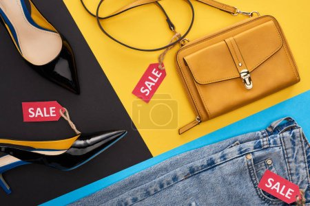 Photo for Top view of jeans, shoes and bag with sale labels on blue, yellow and black background - Royalty Free Image