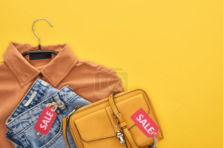 Photo pour Top view of bag, shirt and jeans with sale labels isolated on yellow - image libre de droit