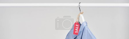 Photo for Blue shirt hanging with sale label isolated on white, panoramic shot - Royalty Free Image