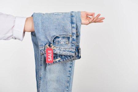 Photo pour Crochet vue d'une femme tenant des jeans suspendus avec étiquette de vente isolée sur blanc - image libre de droit
