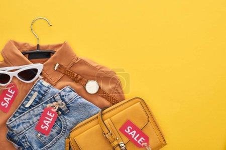 Photo pour Vue de dessus d'un sac, d'une chemise, de lunettes et de jeans isolés en jaune - image libre de droit