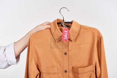 Photo pour Crochet vue d'une femme tenant un cintre avec chemise avec étiquette de vente isolée sur blanc - image libre de droit
