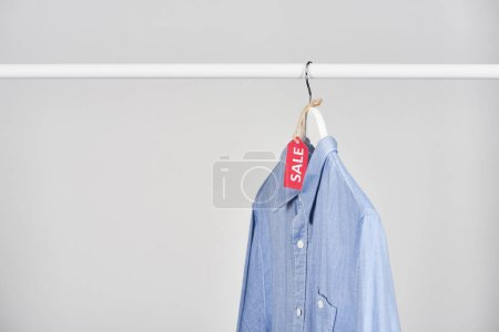 Photo for Blue shirt hanging with sale label isolated on white - Royalty Free Image
