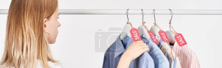Photo pour Blonde woman near elegant shirts hanging with sale labels isolated on white, panoramic shot - image libre de droit