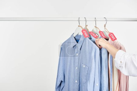 Photo for Cropped view of woman near elegant shirts hanging with sale labels isolated on white - Royalty Free Image