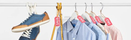 Photo for Sneakers, bag and elegant shirts hanging with sale labels isolated on white, panoramic shot - Royalty Free Image