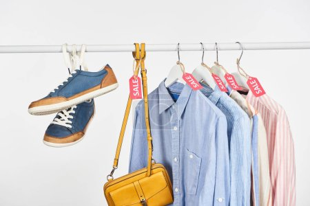 Photo for Sneakers, bag and elegant shirts hanging with sale labels isolated on white - Royalty Free Image