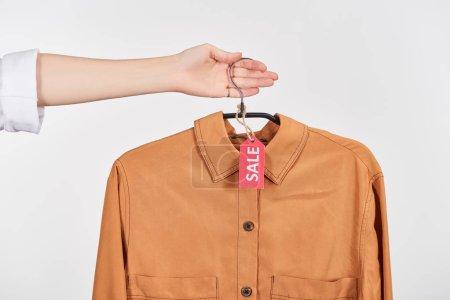 Photo pour Vue en coupe d'une femme tenant une élégante chemise brune avec étiquettes de vente isolées sur - image libre de droit
