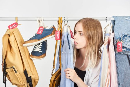 Photo pour Blonde girl in fashionable clothes hanging with sale labels isolated on white - image libre de droit