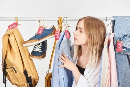 Photo pour Blonde girl in clothes hanging with sale labels isolated on white - image libre de droit