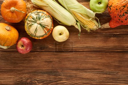 Photo for Top view of raw sweet corn, pumpkins and apples on brown wooden surface - Royalty Free Image