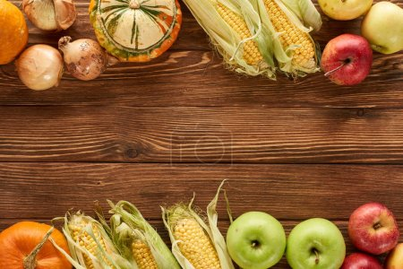 Photo for Top view of raw sweet corn, pumpkins, onions and apples on brown wooden surface - Royalty Free Image