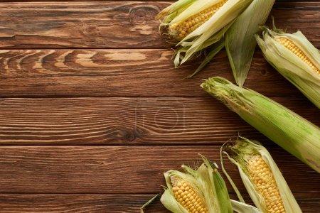 Photo pour Vue supérieure du maïs doux cru sur la surface en bois brun - image libre de droit