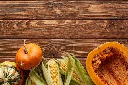 Foto de Vista superior de maíz dulce crudo, calabaza entera y la mitad en la superficie de madera marrón - Imagen libre de derechos