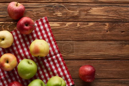 Photo for Top view of checkered tablecloth with fresh apples on wooden surface with copy space - Royalty Free Image