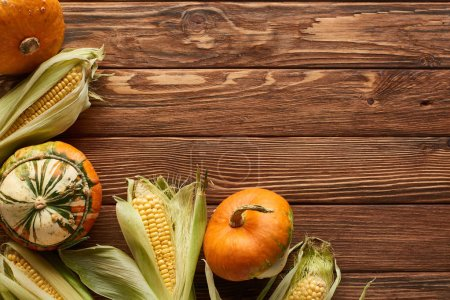Photo for Top view of raw pumpkins and sweet corn on brown wooden surface - Royalty Free Image