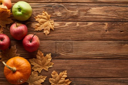 Photo for Top view of small pumpkin and apples on brown wooden surface with dried autumn leaves - Royalty Free Image