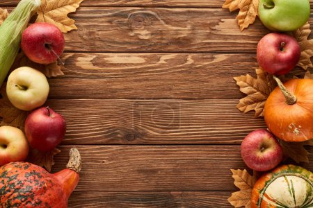 Photo for Top view of pumpkins, sweet corn and apples on wooden surface with dried autumn leaves - Royalty Free Image