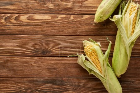 Photo for Top view of uncooked sweet corn on wooden surface - Royalty Free Image