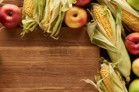 top view of uncooked sweet corn and ripe apples on wooden surface with copy space