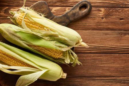 Photo for Top view of brown cutting board with sweet corn on wooden surface with copy space - Royalty Free Image