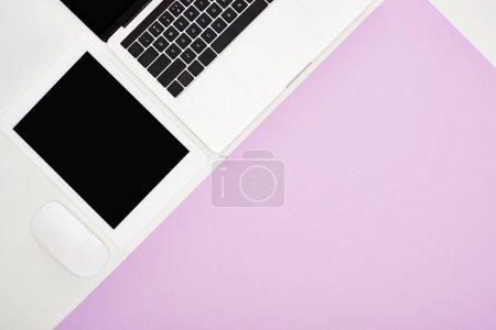 Photo pour Plat avec ordinateur portable, tablette numérique avec écran blanc et souris d'ordinateur sur fond violet et blanc - image libre de droit