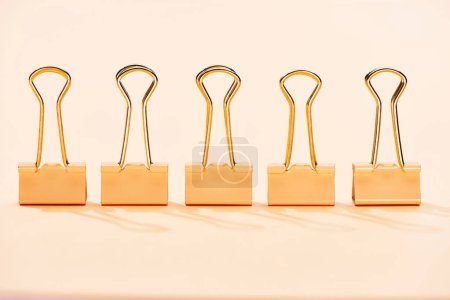Photo for Row of paper clips on beige background with copy space - Royalty Free Image