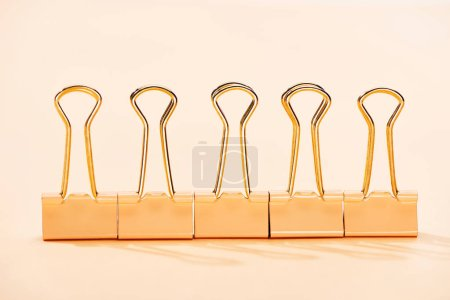 Photo for Row of paper clips on beige background - Royalty Free Image