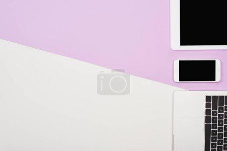 Photo pour Plat gisait avec ordinateur portable, tablette numérique avec écran blanc et smartphone sur fond violet et blanc - image libre de droit