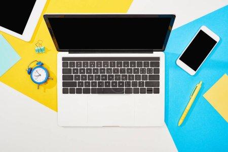 Photo pour Vue du haut de l'ordinateur portable, smartphone, tablette numérique avec écran blanc avec des fournitures de bureau sur fond jaune, bleu et blanc - image libre de droit