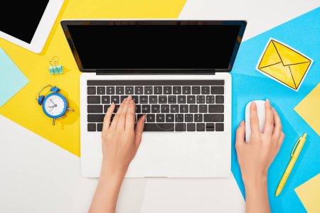 Photo pour Vue recadrée de la femme à l'aide d'un ordinateur portable près des fournitures de bureau et icône du courrier sur fond jaune, bleu et blanc - image libre de droit