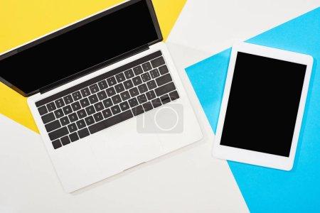 Photo pour Vue du dessus de l'ordinateur portable, tablette numérique avec écran blanc sur fond jaune, bleu et blanc - image libre de droit