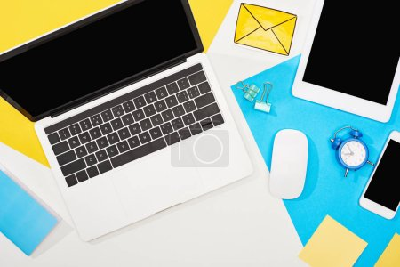Photo for Top view of digital devices with office supplies and mail icon on yellow, blue and white background - Royalty Free Image