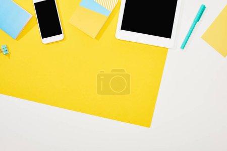 Photo pour Vue du haut du smartphone, tablette numérique avec écran blanc avec des fournitures de bureau sur fond jaune et blanc - image libre de droit