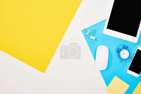 Photo pour Vue du haut du smartphone, tablette numérique avec écran blanc et souris d'ordinateur avec des fournitures de bureau sur fond jaune, bleu et blanc - image libre de droit