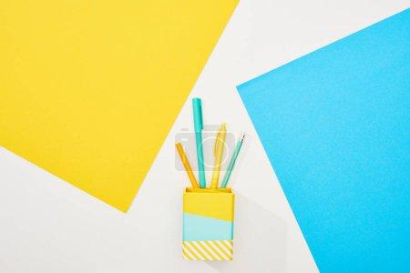 Photo pour Vue supérieure des approvisionnements colorés de bureau sur le fond jaune, bleu et blanc - image libre de droit