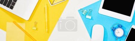 Photo pour Vue du haut de l'ordinateur portatif, smartphone, tablette numérique avec écran blanc et souris d'ordinateur avec des fournitures de bureau sur le fond jaune, bleu et blanc - image libre de droit