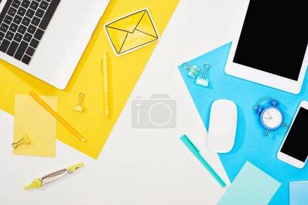 Photo pour Vue supérieure des gadgets avec des approvisionnements de bureau sur le fond jaune, bleu et blanc - image libre de droit