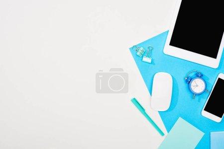 Photo pour Vue du haut du smartphone, tablette numérique avec écran blanc et souris d'ordinateur avec des fournitures de bureau sur fond bleu et blanc - image libre de droit
